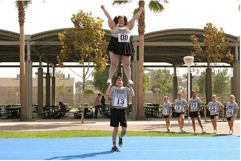 Justin tries to hold up the largest cheerleader