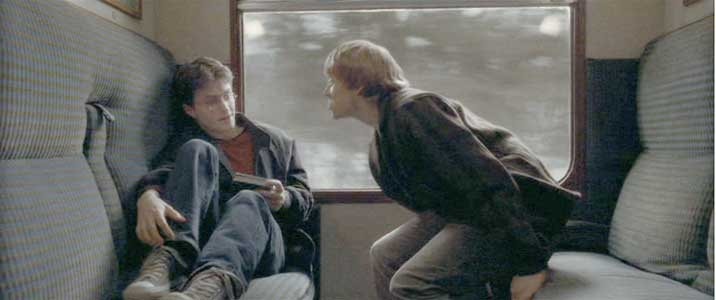 Ron talks to Harry in a train car