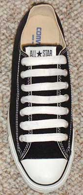 Wide shoelaces on a black low cut