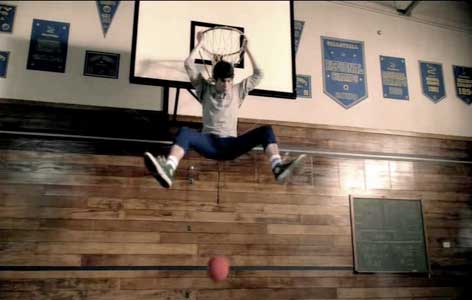 Tyler leaps up and hangs from the basketball hoop
